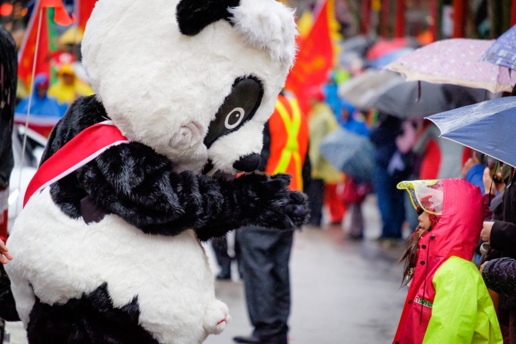 Panda mascot waving to a young girl